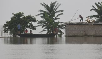 A flood affected girl standing on the roof of a house takes help to board on a boat in Katahguri village along river Brahmaputra, east of Gauhati, India, Sunday, July 14, 2019. Officials in northeastern India said more than a dozen people were killed and over a million affected by flooding. Rain-triggered floods, mudslides and lightning have left a trail of destruction in other parts of South Asia. (AP Photo/Anupam Nath)