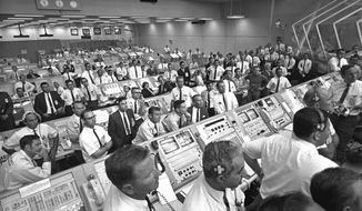 "This July 1969 photo provided by NASA shows launch controllers in the firing room at the Kennedy Space Center in Florida during the Apollo 11 mission to the moon. In the third row from foreground at center is JoAnn Morgan, the first female launch controller. ""I was there. I wasn't going anywhere. I had a real passion for it,"" Morgan said in a July 2019 interview. ""Finally, 99 percent of them accepted that 'JoAnn's here and we're stuck with her.' "" (NASA via AP)"