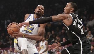 FILE - In this Oct. 28, 2018, file photo, Brooklyn Nets' Caris LeVert (22) defends against Golden State Warriors' Kevin Durant during the first half of an NBA basketball game in New York. Durant and Kyrie Irving gave the Nets two big victories in one night. In the first hours of free agency, the team added two of the best players available to a young roster that made the playoffs, giving them hope of not only contention for an NBA title, but to be the biggest basketball team in New York. (AP Photo/Frank Franklin II, File)