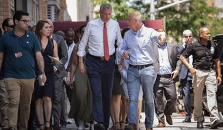New York Mayor Bill de Blasio, center left, listens to Con Ed President Tim Cawley, Sunday, July 14, 2019, as the mayor visits the site of Saturday night's power outage, on New York's Upper West Side. Con Ed says a power outage that left parts of Manhattan in the dark for several hours didn't have anything to do with demand on the electrical grid. Cawley says the cause of the Saturday night outage is still under investigation. (Michael Appleton/Mayoral Photography Office via AP)