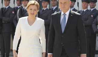 Polish President Andrzej Duda, right, and Slovakian President Zuzana Caputova, left, attend a military welcome ceremony at the presidential Palace in Warsaw, Poland, Monday, July 15, 2019. Caputova is staying for an official visit in Poland. (AP Photo/Czarek Sokolowski)