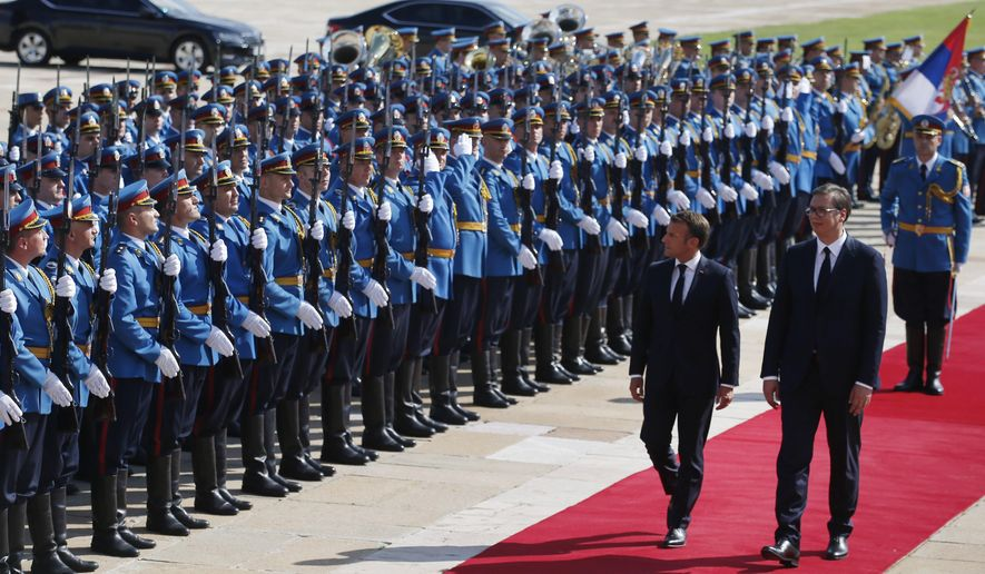 French President Emmanuel Macron, left, and Serbian President Aleksandar Vucic review the honor guards during a welcome ceremony ahead of their meeting in Belgrade, Serbia, Monday, July 15, 2019. French President Emmanuel Macron is for a two days official visit in Belgrade. (AP Photo/Darko Vojinovic)