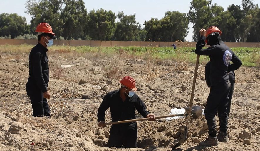 This Sunday, July 14, 2019 frame grab from video, shows Syrian workers of the Civil Council of Raqqa digging for human remains at the site of a mass grave believed to contain the bodies of civilians and Islamic State militants, in Raqqa. A local official in Syria's Raqqa says workers have unearthed 313 bodies from a mass grave since it was discovered last month near the northern city. Yasser al-Khamees who leads a team of first responders says among the bodies found are those belonging to civilians, including women and children, as well as people believed to have been shot dead by IS militants. (AP Photo)
