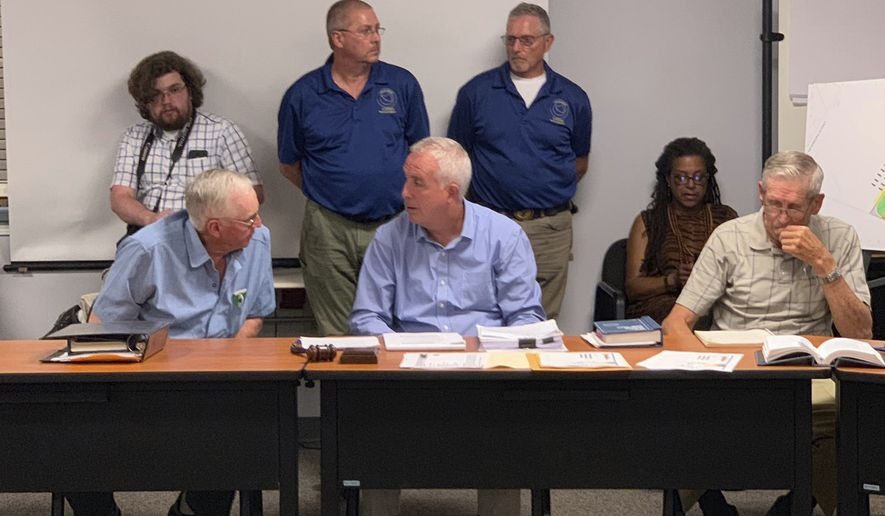 Members of the Vernon, N.Y., Planning Board are seated at the table at Vernon Town Hall, in Vernon, N.Y., Tuesday, July 16, 2019. According to the Utica Observer-Dispatch, the planning board denied a permit to Woodstock 50 organizers for a second time as they sought to hold a music festival at a local horse track in August. (Edward Harris/Observer-Dispatch via AP)