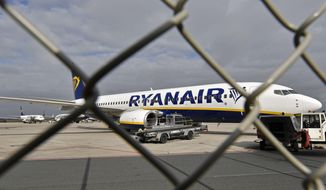 FILE - In this Wednesday, Sept. 12, 2018 file photo, a Ryanair plane is parked at the airport in Weeze, Germany. Europe's biggest airline by passengers, budget carrier Ryanair, will cut flights and close some of its bases beginning this winter because of the delay to deliveries of the Boeing 737 Max plane, which has been grounded globally after two fatal crashes. The airline warned Tuesday, July 16, 2019, its growth in European summer traffic for 2020 will be lower than expected because of the slowed deliveries. (AP Photo/Martin Meissner, File)