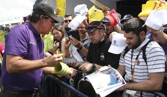Phil Mickelson of the United States signs autographs on the 18th fairway during a practice round ahead of the start of the British Open golf championships at Royal Portrush in Northern Ireland, Tuesday, July 16, 2019. The British Open starts Thursday. (AP Photo/Peter Morrison)