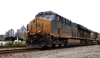 In this June 24, 2019, photo a CSX freight train rolls past downtown Pittsburgh. CSX Corp. reports financial results on Tuesday, July 16. (AP Photo/Gene J. Puskar)