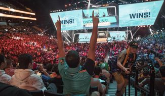 FILE - In this July 28, 2018, file photo, London Spitfire fan Rick Ybarra, of Plainfield, Ind., reacts after London won the second game against the Philadelphia Fusion during the Overwatch League Grand Finals competition at Barclays Center in New York. Each Overwatch League franchise will host two to five homestand weekends in 2020 as the esports league launches an unprecedented home-and-away schedule spanning three continents. The esport league revealed Tuesday, July 16, 2019, plans for each of its 20 teams to host homestand series, similar to events staged by teams this year in Dallas, Atlanta and Los Angeles, as part of its 2020 regular season.(AP Photo/Mary Altaffer, File)