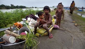 Flood affected children sit near their belongings on an embankment in Pabhokathi village east of Gauhati India, Monday, July 15, 2019. After causing flooding and landslides in Nepal, three rivers are overflowing in northeastern India and submerging parts of the region, affecting the lives of more than 2 million, officials said Monday.(AP Photo/Anupam Nath)