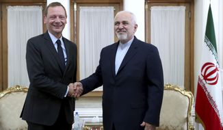 """Iranian Foreign Minister Mohammad Javad Zarif, right, shakes hand with French presidential envoy Emmanuel Bonne, as they pose for photos, in Tehran, Iran, Wednesday, July 10, 2019. France sent Bonne to Tehran to urge Iran to return to complying with the terms of the deal """"without delay."""" (AP Photo/Ebrahim Noroozi)"""