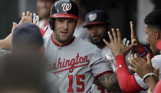 Washington Nationals' Matt Adams is greeted in the dugout after hitting a solo home run off Baltimore Orioles starting pitcher Asher Wojciechowski during the second inning of a baseball game, Tuesday, July 16, 2019, in Baltimore. (AP Photo/Julio Cortez)