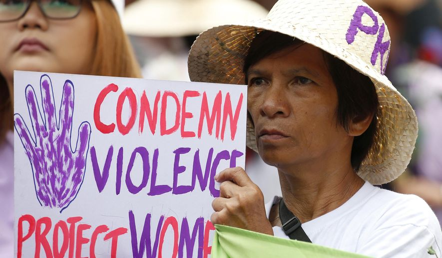 FILE - In this March 8, 2018, file photo, a protester displays a placard during a rally to mark International Women's Day which largely turns out to be an anti-government event in Manila, Philippines. The Philippine president signed Tuesday, July 16, 2019 a bill into law penalizing a range of acts of sexual harassment including catcalling, wolf-whistling and persistent telling of sexual jokes, which pro-women's groups have accused him of committing.  (AP Photo/Bullit Marquez, File)