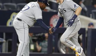 Tampa Bay Rays' third base coach Rodney Linares, left, congratulates Travis d'Arnaud after d'Arnaud hit a three-run home run off New York Yankees' closer Aroldis Chapma during the ninth inning of a baseball game, Monday, July 15, 2019, in New York. (AP Photo/Kathy Willens)