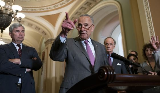 Senate Minority Leader Chuck Schumer, D-N.Y., flanked by Sen. Sheldon Whitehouse, D-R.I., left, and Sen. Tom Carper, D-Del., condemns remarks by President Donald Trump as he speaks to reporters following a Democratic policy meeting, at the Capitol in Washington, Tuesday, July 16, 2019. (AP Photo/J. Scott Applewhite)