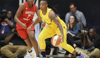 FILE - In this Thursday, Aug. 23, 2018 file photo, Los Angeles Sparks guard Riquna Williams, right, dribbles against Washington Mystics guard Ariel Atkins (7) in the first half of a single elimination WNBA basketball playoff game in Washington. The WNBA has suspended Los Angeles Sparks guard Riquna Williams 10 games for a domestic violence incident, the longest suspension in league history. The WNBA handed down the suspension Tuesday, July 16, 2019. (AP Photo/Nick Wass) ** FILE **