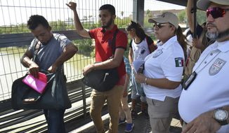 Mexican migration officers escort a group of migrants to apply for asylum in the United States, on the International Bridge 1 in Nuevo Laredo, Mexico, Wednesday, July 17, 2019. Asylum-seekers grappled to understand what a new U.S. policy that all but eliminates refugee claims by Central Americans and many others meant for their bids to find a better life in America amid a chaos of rumors, confusion and fear. (AP Photo/AP Photo/Salvador Gonzalez)