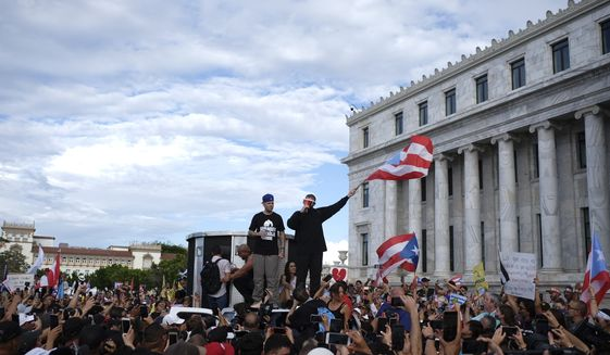 Puerto Rican rapper Rene Juan Perez known by his stage name Residente and Benito Antonio Martinez Ocasio, known by his stage name Bad Bunny, warm up the crowd in front of the Puerto Rican Capitol, before a protest march against governor Ricardo Rosello, in San Juan, Puerto Rico, Wednesday, July 17, 2019. Protesters are demanding Rosselló step down for his involvement in a private chat in which he used profanities to describe an ex-New York City councilwoman and a federal control board overseeing the island's finance. (AP Photo/Dennis M. Rivera Pichardo)