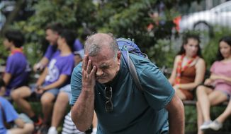 Russ Wilson splashes water on his face from a fountain in New York, Wednesday, July 17, 2019. The heat wave that has been roasting much of the U.S. in recent days is just getting warmed up, with temperatures expected to soar to dangerous levels through the weekend. (AP Photo/Seth Wenig)