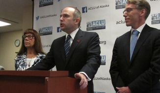 Joshua Decker, center, director of the ACLU of Alaska, speaks at a press conference with Bonnie Jack, left, and John Kauffman on Wednesday, July 17, 2019, in Anchorage, Alaska. ACLU of Alaska is representing Jack and Kauffman in a lawsuit filed against Alaska Gov. Mike Dunleavy for his veto of $334,700 from the Alaska Court System budget. (AP Photo/Dan Joling)