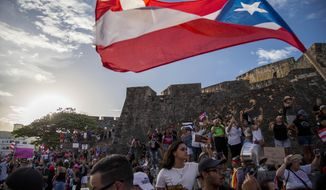Demonstrators march against governor Ricardo Rosello, in San Juan, Puerto Rico, Wednesday, July 17, 2019. Protesters are demanding Rossello step down for his involvement in a private chat in which he used profanities to describe an ex-New York City councilwoman and a federal control board overseeing the island's finance. (AP Photo/Dennis M. Rivera Pichardo)