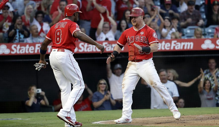 Los Angeles Angels' Kole Calhoun, right, celebrates with Justin Upton (8) after they scored on a double by Albert Pujols during the first inning of a baseball game against the Houston Astros on Tuesday, July 16, 2019, in Anaheim, Calif. (AP Photo/Marcio Jose Sanchez)