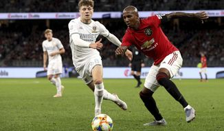 Ashley Young, right, of Manchester United and Jordan Stevens of Leeds United compete for the ball during their friendly soccer match in Perth, Australia, Wednesday, July 17, 2019. (Richard Wainwright/AAP Image via AP)