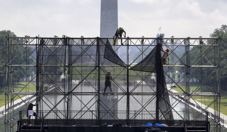 """FILE - In this July 5, 2019, file photo workers dismantle a riser, with the Washington Monument and Lincoln Memorial Reflecting Pool behind, as clean up is underway after Fourth of July celebrations in Washington. On Wednesday, July 17, the Federal Reserve releases its latest """"Beige Book"""" survey of economic conditions. (AP Photo/Alex Brandon, File)"""