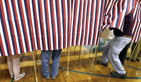 A voter enters a booth at a polling place in Exeter, N.H. On Sunday, Nov. 27. (AP Photo/Elise Amendola, File)