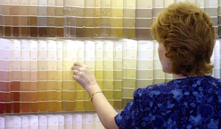 FILE - In this June 28, 2004, file photo, a customer looks over color chips at a Sherwin-Williams store in Columbus, Ohio. The nation's major suppliers of lead paint have agreed to pay California's largest cities and counties $305 million to settle a nearly two-decade old lawsuit. The settlement announced Wednesday, July 17, 2019, comes after years of legal and legislative battling in California and other states. The settlement is with the Sherwin-Williams Company, ConAgra Grocery Products Company and NL Industries, Inc. (AP Photo/Jay LaPrete, File)