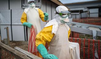 In this photograph taken Saturday July 13, 2019, health workers wearing protective suits take their shift at a treatment center in Beni, Congo DRC. The head of the World Health Organization is convening a meeting of experts Wednesday July 17, 2019 to decide whether the Ebola outbreak should be declared an international emergency after spreading to eastern Congo's biggest city, Goma, this week. More than 1,600 people in eastern Congo have died as the virus has spread in areas too dangerous for health teams to access.(AP Photo/Jerome Delay)