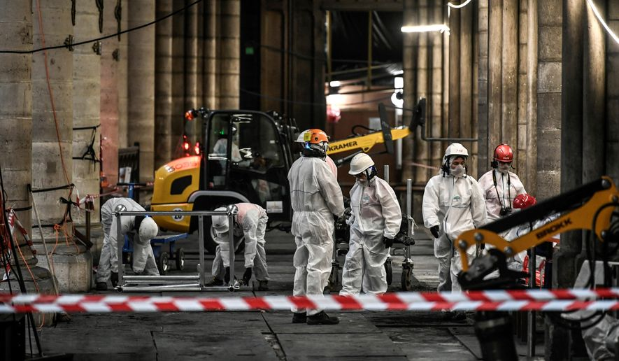 Workers are pictured during preliminary work at the Notre-Dame de Paris Cathedral, Wednesday, July 17, 2019, in Paris. The chief architect of France's historic monuments says that three months after the April 15 fire that devastated Notre Dame Cathedral the site is still being secured. (Stephane de Sakutin/Pool via AP)