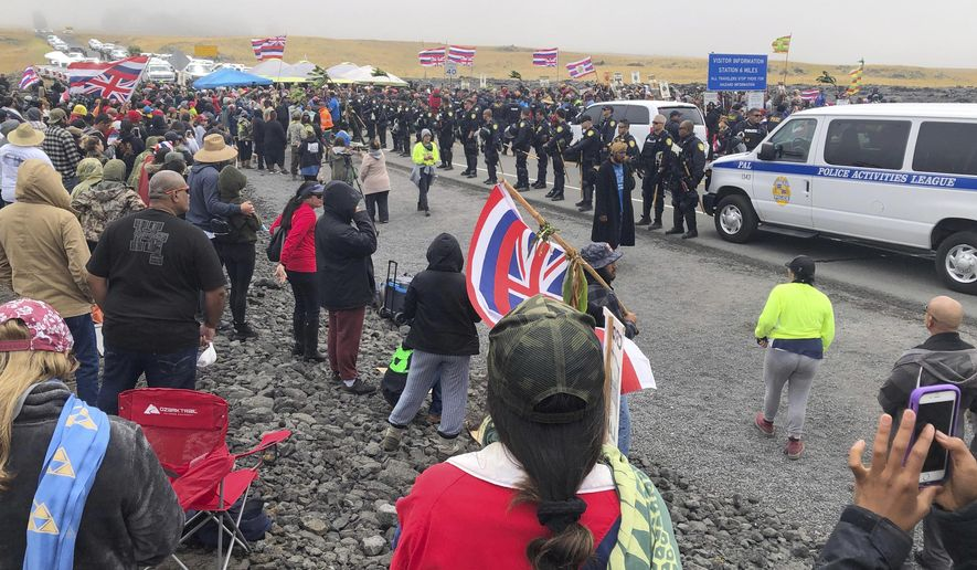 Police in riot gear are lined up on a road in Hawaii where an estimated 2,000 people are gathered to protest construction of a telescope on a mountain that some Native Hawaiians consider sacred, on Mauna Kea on the Big Island of Hawaii, Wednesday, July 17, 2019. Hawaii County Managing Director Wil Okabe says officials on Wednesday closed a highway leading to the protest site so a convoy of construction equipment can be brought up Mauna Kea. Protesters are off to the side of the road, singing. (Cindy Ellen Russell/Honolulu Star-Advertiser via AP)