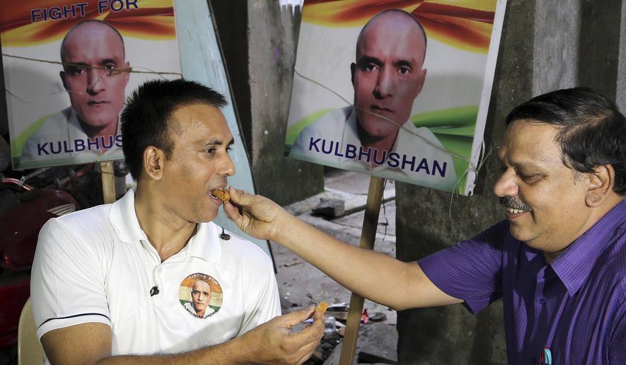 Indian friends of Kulbhushan Jadhav, share sweets as they celebrate verdict of International Court of Justice in Mumbai, India, Wednesday, July 17, 2019. The United Nations' highest court has ordered that Pakistan stay the execution of Jadhav, an alleged Indian spy and ordered that his case be reviewed after agreeing with India's contention that his rights had been violated. (AP Photo/Rajanish Kakade)