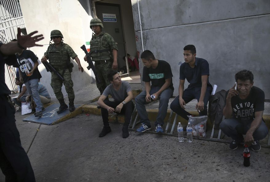 Migrants wait under guard at an immigration center on the International Bridge 1, as an immigration agent attempts to block the camera,  in Nuevo Laredo, Mexico, Tuesday, July 16, 2019. A U.S. policy to make asylum seekers wait in Mexico while their cases wind through clogged U.S. immigration courts has also expanded to the violent city of Nuevo Laredo. The group was returned from the U.S. after being detained. (AP Photo/Marco Ugarte)