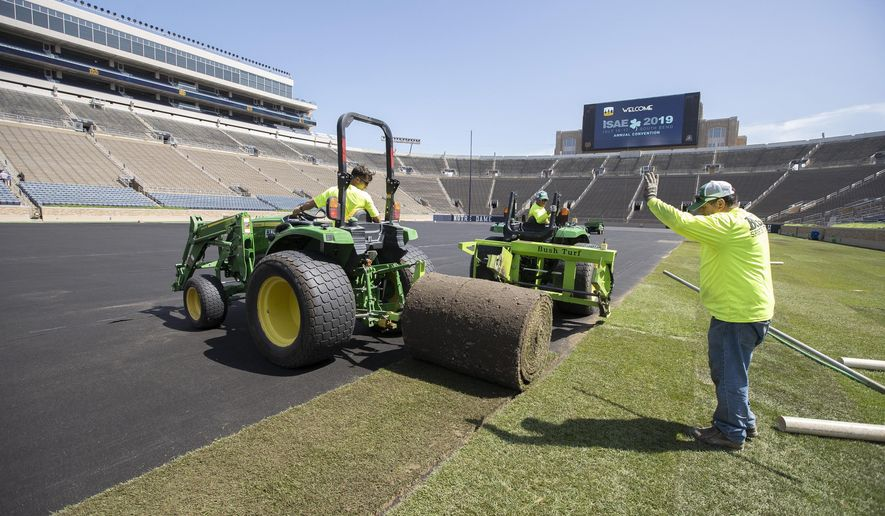 Natural turf is installed at Notre Dame Stadium in preparation for a professional soccer match in South Bend, Ind., Monday, July 15, 2019. Crews began unrolling large rolls of turf at the stadium Monday ahead of Friday's scheduled friendly matchup between Liverpool F.C. and Borussia Dortmund. (Santiago Flores/South Bend Tribune via AP)