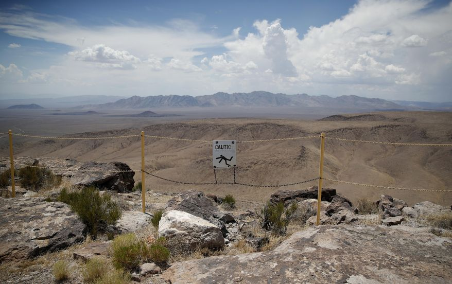 FILE - In this July 14, 2018, file photo, a sign warns of a falling danger on the crest of Yucca Mountain during a congressional tour near Mercury, Nev. Nevada's governor and congressional delegation say recent earthquakes should make the U.S. Energy Department look again at seismic risks at a site eyed as the place to bury the nation's nuclear waste, Wednesday, July 17, 2019. (AP Photo/John Locher, File)