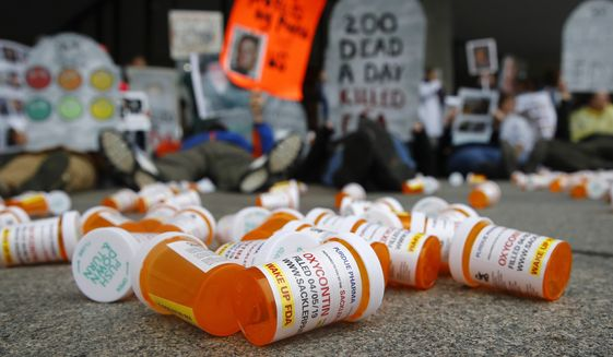 In this April 5, 2019, file photo, containers depicting OxyContin prescription pill bottles lie on the ground in front of the Department of Health and Human Services' headquarters in Washington as protesters demonstrate against the FDA's opioid prescription drug approval practices. (AP Photo/Patrick Semansky, File)