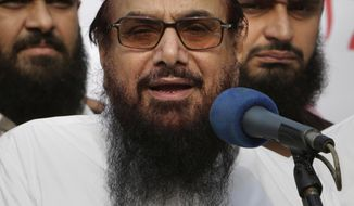 FILE - In this Friday, Oct. 26, 2018 file photo, Hafiz Saeed, founder of Pakistani religious group Jamaat-ud-Dawa addresses an anti-Indian rally in Lahore, Pakistan. Pakistani authorities say they have arrested Saeed, a radical cleric and U.S.-wanted terror suspect blamed for the 2008 Mumbai attacks, just days ahead of Prime Minister Imran Khan's trip to Washington. (AP Photo/K.M. Chaudary, File)