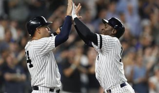 New York Yankees' Gary Sanchez, left, congratulates Didi Gregorius after scoring on Gregorius' grand slam during the eighth inning of the team's baseball game against the Tampa Bay Rays, Tuesday, July 16, 2019, in New York. (AP Photo/Kathy Willens)