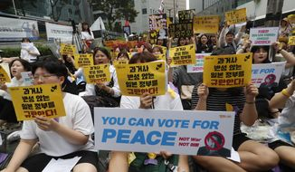 "Protesters shout slogans during a rally demanding full compensation and an apology for wartime sex slaves from Japanese government in front of the Japanese Embassy in Seoul, Wednesday, July 17, 2019. In his strongest comments yet on a growing trade dispute, South Korean President Moon Jae-in urged Japan on Monday to lift recently tightened controls on high-tech exports to South Korea, which he said threaten to shatter the countries' economic cooperation and could damage Japan more than South Korea. The signs read: ""Apology and compensation."" (AP Photo/Ahn Young-joon)"