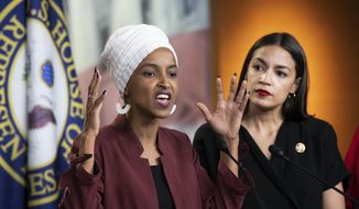"""U.S. Rep. Ilhan Omar, D-Minn., left, joined at right by U.S. Rep. Alexandria Ocasio-Cortez, D-N.Y., responds to base remarks by President Donald Trump after he called for four Democratic congresswomen of color to go back to their """"broken"""" countries, as he exploited the nation's glaring racial divisions once again for political gain, during a news conference at the Capitol in Washington, Monday, July 15, 2019. All four congresswomen are American citizens and three of the four were born in the U.S. Omar is the first Somali-American in Congress. (AP Photo/J. Scott Applewhite)"""