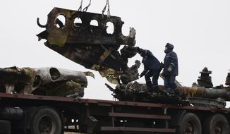 FILE - In this file photo dated Sunday, Nov. 16, 2014, recovery workers in rebel-controlled eastern Ukraine load debris from the crash site of Malaysia Airlines Flight 17, in Hrabove, Ukraine, with recovery operations carried out under the supervision of Dutch investigators and officials from the Organization for Security and Cooperation in Europe.  Five years after a missile blew Malaysia Airlines Flight 17 out of the sky above eastern Ukraine, relatives and friends of those killed will gather Wednesday July 17, 2019, at a Dutch memorial to mark the anniversary.(AP Photo/Mstyslav Chernov, FILE)