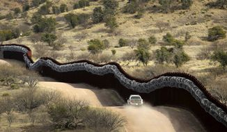 A Customs and Border Control agent patrols the defining line between the U.S. and Mexico near Nogales, Arizona, — far from the noise of immigration arguments on Capitol Hill and elsewhere. (Associated Press)