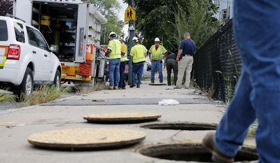 In this Sept. 14, 2018, photo, a worker with Columbia gas stands over an open manhole as the crew works to make sure there are no gas leaks at the corner of Parker and Salem Streets in Lawrence, Mass. The series of natural gas explosions and fires in Massachusetts last September has cost provider Columbia Gas of Massachusetts more than $1 billion. (AP Photo/(AP Photo/Mary Schwalm) **FILE**