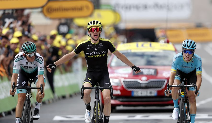 Britain's Simon Yates, center, surrounded by Spain's Pello Bilbao Lopez De Armentia, right, and Austria's Gregor Muhlberger, celebrates as he crosses the finish line to win the twelfth stage of the Tour de France cycling race over 209,5 kilometers (130 miles) with start in Toulouse and finish in Bagneres-de-Bigorre, France, Thursday, July 18, 2019. (AP Photo/ Thibault Camus)