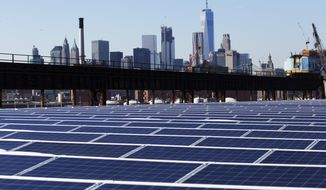 FILE - In this Feb. 14, 2017, file photo, a rooftop is covered with solar panels at the Brooklyn Navy Yard in New York. The Manhattan skyline is at top. A new law signed Thursday by New York Gov. Andrew Cuomo sets the nation's most aggressive targets for reducing carbon emissions and is intended to drive dramatic changes over the next 30 years. It calls for all the state's electricity to come from renewable, carbon-free sources such as solar, wind and hydropower. Transportation and building heating systems would also run on clean electricity rather than oil and gas. (AP Photo/Mark Lennihan, File)