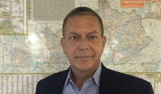 This Monday, July 15, 2019 photo shows Democrat Mike Broihier standing in front of the map of Kentucky at The Associated Press bureau in Louisville, Ky.  Broihier announced his candidacy for the Democratic nomination for the U.S. Senate seat held by Senate Majority Leader Mitch McConnell on Thursday, July 18. Broihier is a first-time candidate with a broad resume as a Marine officer, farmer and small-town newspaperman. (AP Photo/Bruce Schreiner)