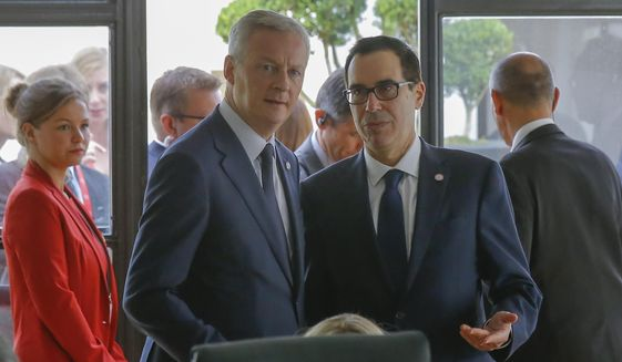 French Finance Minister Bruno Le Maire, left, talks to U.S. Treasury Secretary Steve Mnuchin during a meeting at the G-7 Finance in Chantilly, north of Paris, on Thursday, July 18, 2019. (AP Photo/Michel Euler)