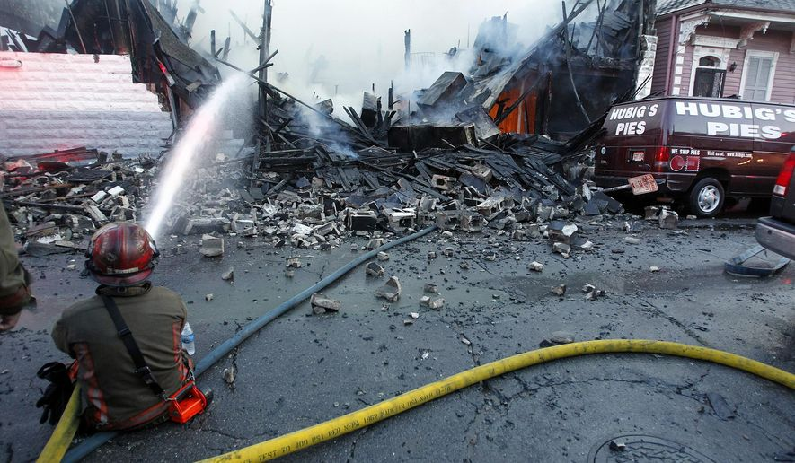 FILE - In a Friday, July 27, 2012 file photo, New Orleans firefighters work to put out a fire at Hubig's Pies in New Orleans. Louisiana's economic development office announced Thursday, July 18, 2019 that Hubig's Pies will be produced again in 2020 in suburban Jefferson Parish. (Catherine Threlkeld/The Times-Picayune/The New Orleans Advocate via AP)