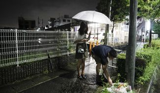 "A couple places flowers near the Kyoto Animation building, Friday, July 19, 2019, background left, that was destroyed in an arson attack in Kyoto, Japan.  A man screaming ""You die!"" burst into an animation studio in Kyoto, doused it with a flammable liquid and set it on fire Thursday, killing several people in an attack that shocked the country and brought an outpouring of grief from anime fans. (AP Photo/Jae C. Hong)"